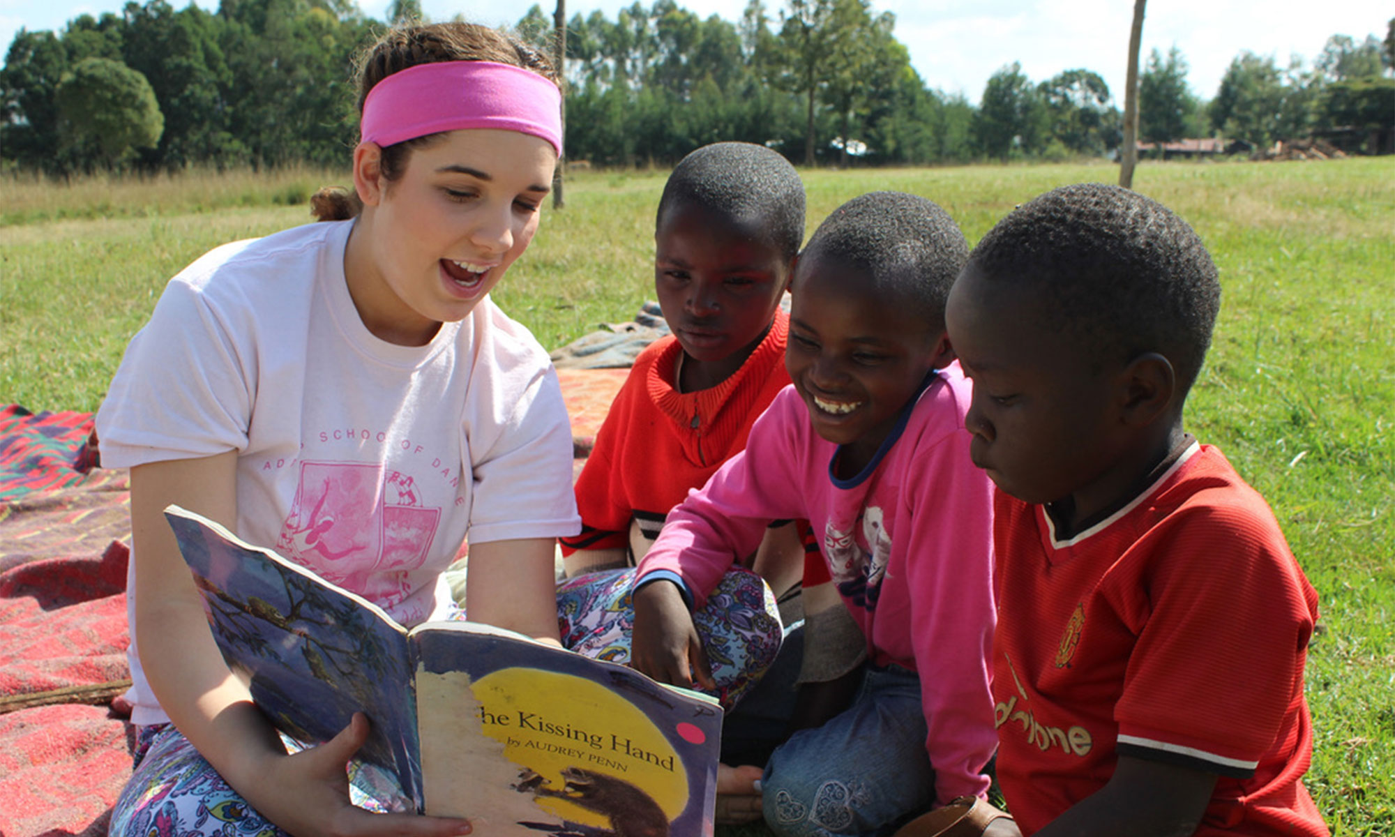 volunteer reading to children at Rapha Community Center